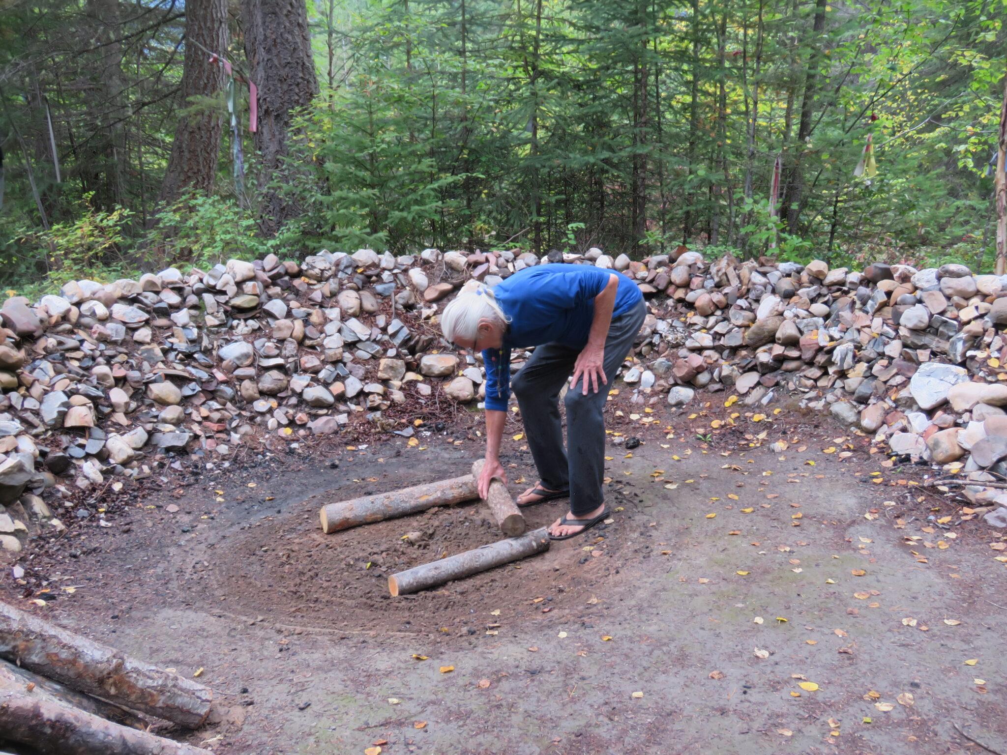 Sequoyah bereitet die Basis für das Feuer für die Schwitzhütte vor