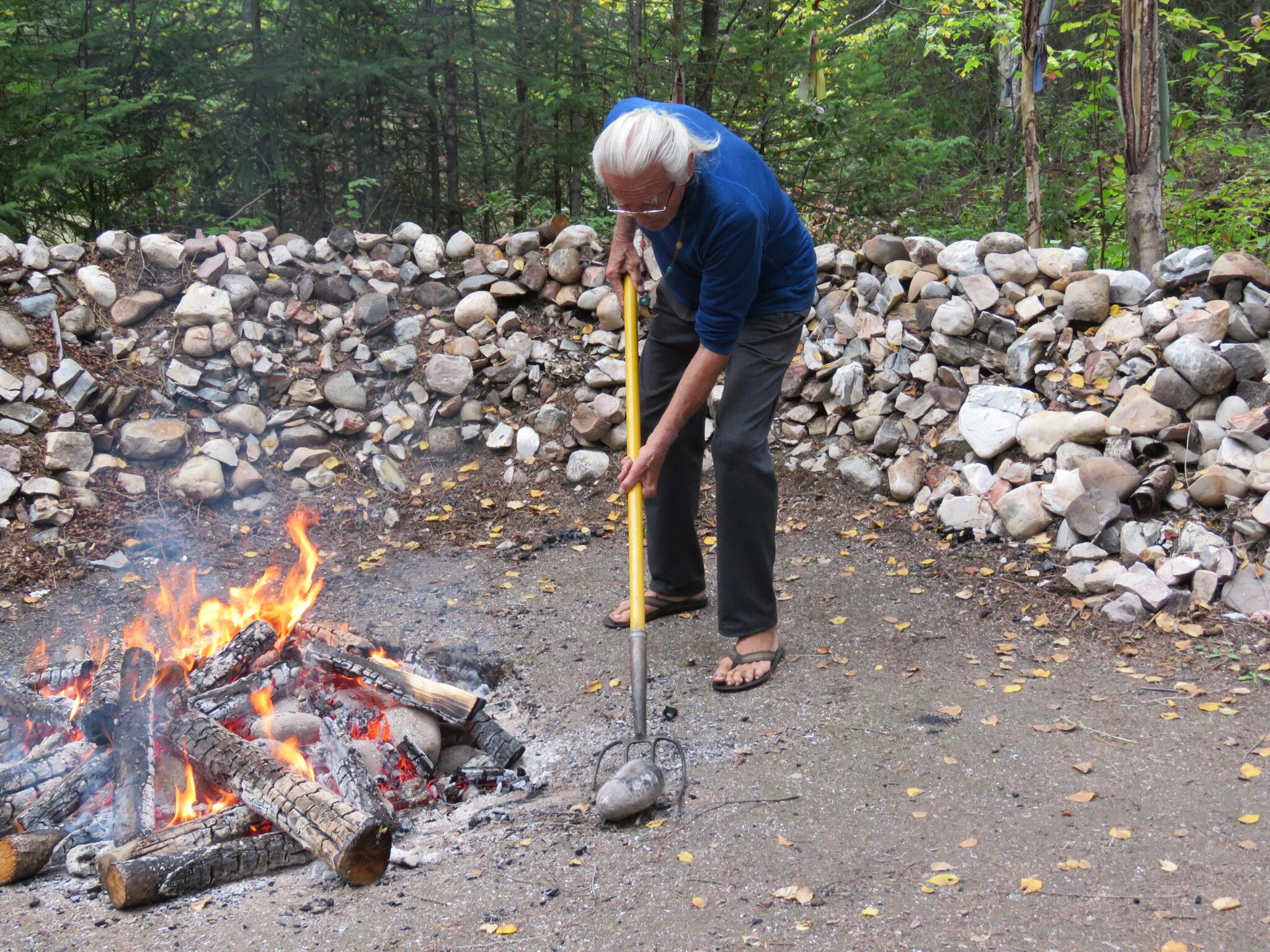 Feuer Schwitzhütte - Sequoyah holt die glühend heissen Steine aus dem FEuer und bringt diese in die Schwitzhütt